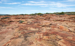 Red Bluff: Rugged Terrain. Landscape with rugged, red sandstone terrain at Red Bluff under a blue sky with clouds on the coral coast in Kalbarri, Western stock photos