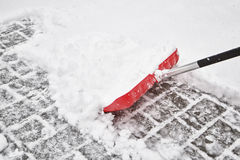 Red blurry snow shovel. For snow removal in deep fresh snow at snowy day Royalty Free Stock Photos