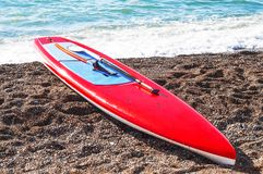 Red board for stand up paddle surfing SUP. On the beach royalty free stock photography