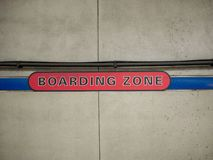 Red boarding zone sign on concrete wall in subway station royalty free stock images
