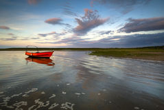 Red boat. Lone red boat, taken at sunset just as the tide was comming in. Blakeney, Norfolk, UK Stock Image