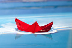 Red boat. Red paper boat on blue water stock photos