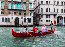 Red Boat. Venice,Italy- February 19, 2012: A red boat with a group of funny disguised people sailing on the Grand Canal in a boats parade during the Carnival Stock Photography