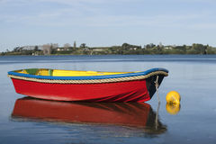 Red boat. Small bright red boat floating on calm water stock photos