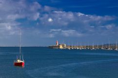 Red Boat. In blue waters with pier and lighthouse in distance in Dun Laoghaire Harbour, Ireland royalty free stock photo