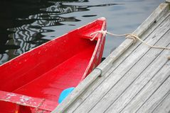 Red boat. Old red row boat tied to a pier in Perkins Cove, Maine stock image