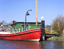 Red boat anchored on a wooden jetty or pier. Stock Photo