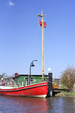 Red boat anchored on a wooden jetty or pier. Royalty Free Stock Photos