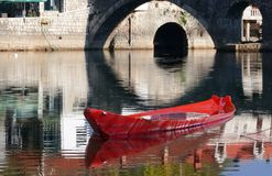 Red boat in ancient autumn lake. Stone bridge. Royalty Free Stock Photo