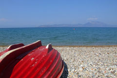 Red boat on beach. A view of a small red boat pulled onto the beach upside down on the shore of the Corinthian Gulf, Pelopones, Greece Royalty Free Stock Photo
