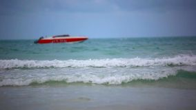 Red boat on a beach. Sea waves during cloudy. Weather. 1920x1080 stock video footage