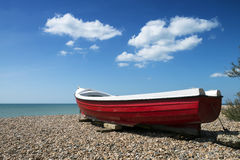 Red Boat on Beach. A red and white painted boat on a pebble beach on a sunny day Stock Photography