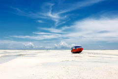 Red boat on the beach of Zanzibar on the blue sky background. Royalty Free Stock Photo