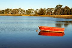 Red boat on a calm lake. Red wood boat floating in a calm lake. Photo taken in Lobos lake, Buenos Aires, Argentina. summer afternoon sunset time. golden hour stock images