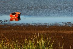 Red boat on a calm lake. Red wood boat floating in a calm lake. Photo taken in Lobos lake, Buenos Aires, Argentina. summer afternoon sunset time. golden hour stock photography