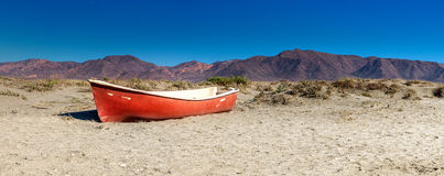 Red boat in desert. Landscape photo: lost red boat in the desert of cabo de gata Andalusia with the mountains in the background stock image