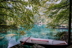 A red boat in green clear clean water lake in Switzerland Stock Photo