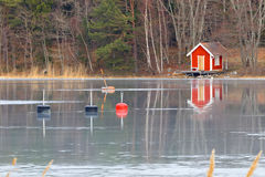 Red boat house reflecting in the ice Royalty Free Stock Image