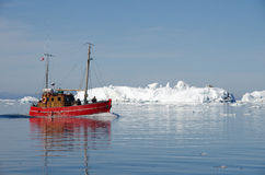 Red boat among the icebergs, Greenland. Red fishing boat carrying tourists among the Icebergs off Ilulissat, Greenland. Tourism is an emerging source of income Royalty Free Stock Image