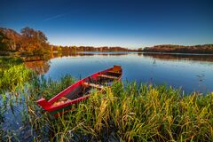 Red boat, lake landscape in fall season