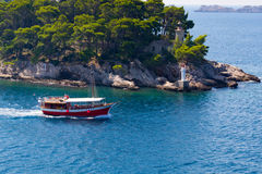 Red boat and lighthouse in water near Dubrovnik Royalty Free Stock Photography