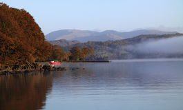 Red boat on misty lake. Red boat moored by the edge of Lake Coniston, Cumbria, England in the early morning mist with views of the Lake District fells beyond royalty free stock photos