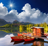 Red boat in a mountain lake. Beautiful red boat in a mountain lake Strbske Pleso, Slovakia, Europe stock image
