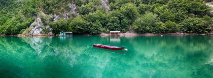 Red boat in the mountain river. Red boat standing still in the mountain river in Serbia stock image