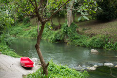 Red boat by mountain stream Royalty Free Stock Photos