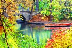 Red boat near stone bridge on lake Stock Images