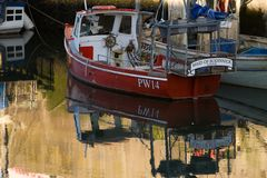 Red boat in Padstow harbour, cornwall. A small red fishing boat in the evening light on a calm sea in Padstow harbour, Cornwall, UK royalty free stock photo
