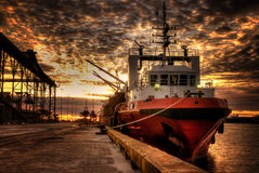 Red boat at port during sunset HDR. Offshore vessel boat berthing at harbor with sunset stock photos