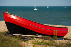 Red boat resting in the sunshine. Waiting for the tide stock photography