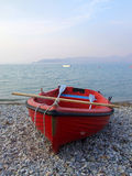 Red boat on rocky beach. A small red boat with oars, is left ashore on a rocky beach in the Gulf of Corinth, Pelopones, Greece Royalty Free Stock Photos