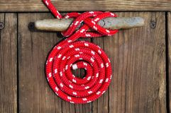 Red Boat Rope. Circle of red rope securing boat to dock stock images