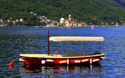 The red  boat  sails on the Bay of Kotor, Montenegro. Stock Image