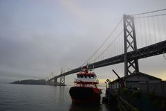 Red Boat 2 and the San Francisco Oakland Bay Bridge. This photo was taken last January 9, 2019, and it was a very cold and very foggy morning stock photo