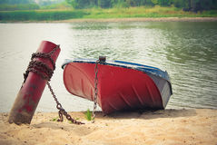 Red boat on the shore. Old red boat chained to a peg on the sandy shore Stock Image