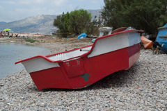 A red boat on the shore of a river Royalty Free Stock Photography