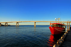 Red Boat. Tied up to a dock with a bridge in the background Stock Image