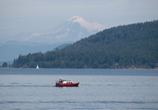 Red boat on waters of Puget sound with Mt. Baker Royalty Free Stock Photos