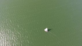 Red boat with white sails sailing on the sea. View from the height. The sun shines brightly. Small waves on the sea. Nobody around stock footage