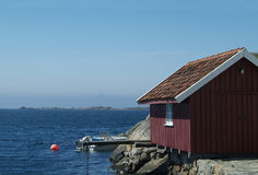 Red boathouse. And open speedboat with outboard engine. Loshavn, Norway Stock Photography
