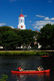 Red boats by Harvard. Red boats passing in front of Harvard Dunster House red dome Stock Photos