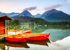 Red boats moored at wooden house on a lake. Royalty Free Stock Images