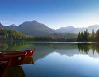 Red boats in mountain lake in High Tatra. Strbske pleso, Slovaki Stock Photo