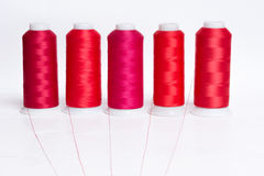Red bobbin thread on white wooden table Royalty Free Stock Image