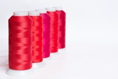 Red bobbin thread on white wooden table Royalty Free Stock Photography