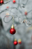 A Red Bobble Christmas Ornament hanging from a wire Royalty Free Stock Image