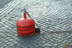 Red bollard with chain on black brick roadway Royalty Free Stock Photo